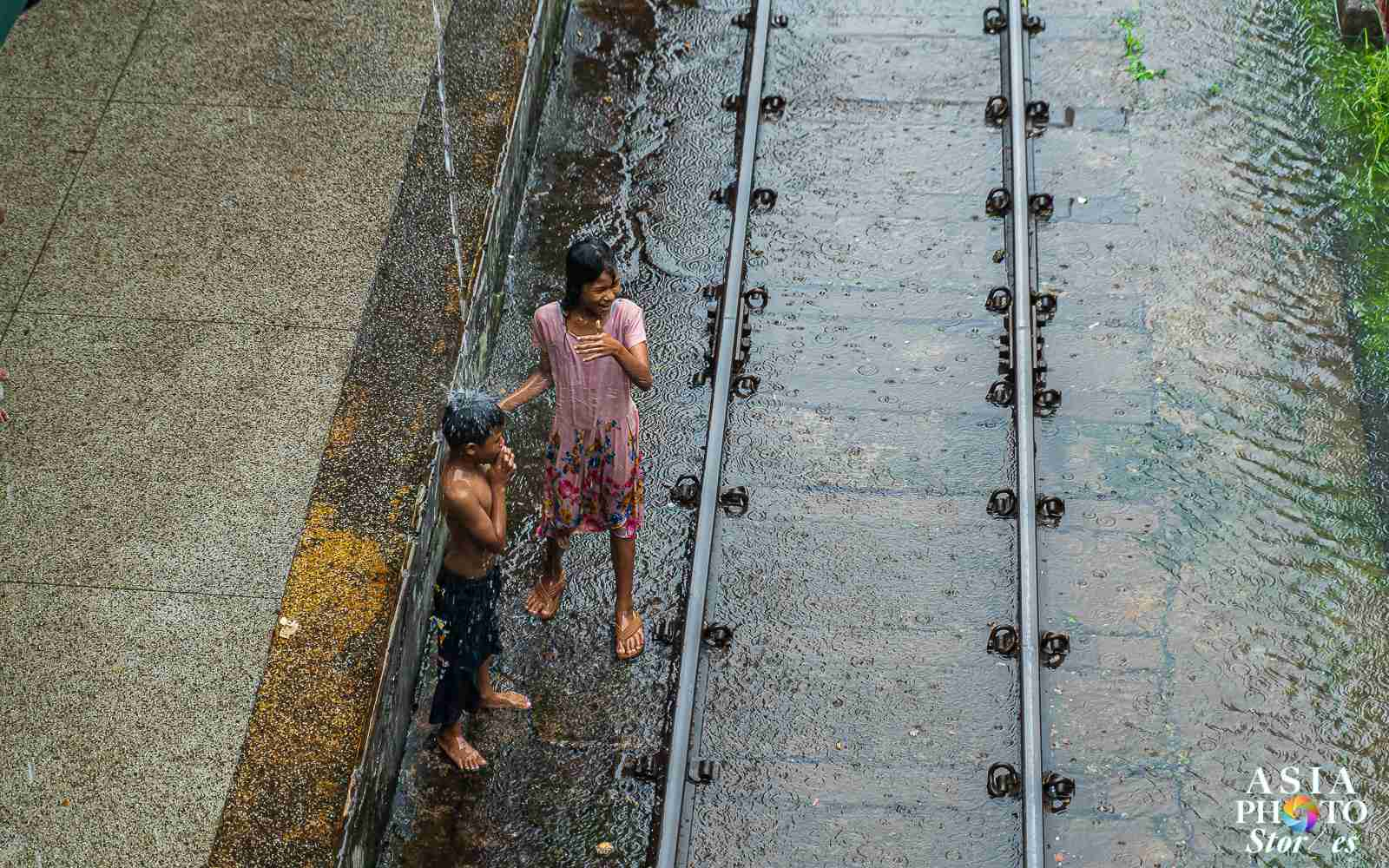 Kids make the most of a heavy downpour at the Yangon Central Rail Station.