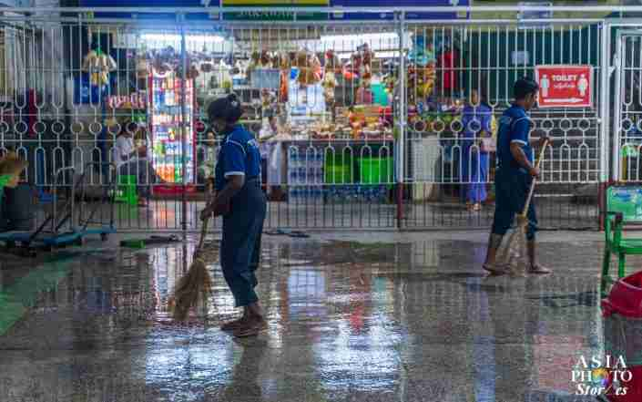 Workers at the Yangon Central Rail Station sweep up after a montrous thunderstorm.