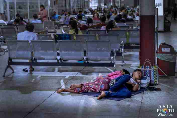 A boy and his mother sleep on the floor while waiting at the Yangon Central Rail Station.