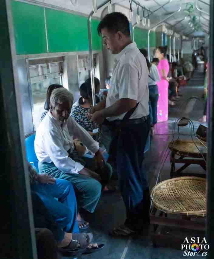 A conductor checks tickets on the Yangon Circle Line.