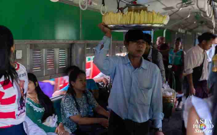 A vendor sells his wares on a Yangon train.
