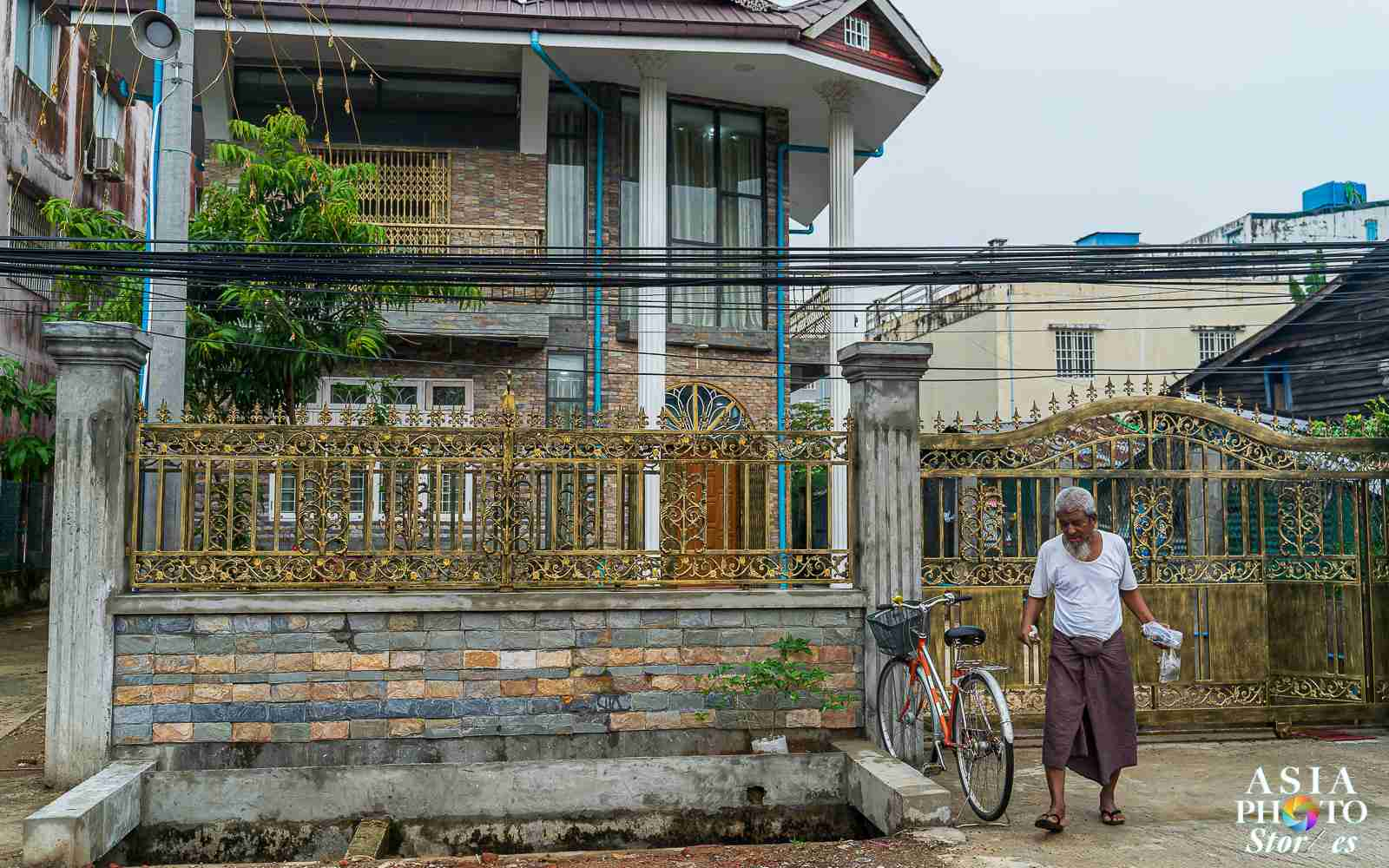 A man stands outside a large house near a Yangon train station.