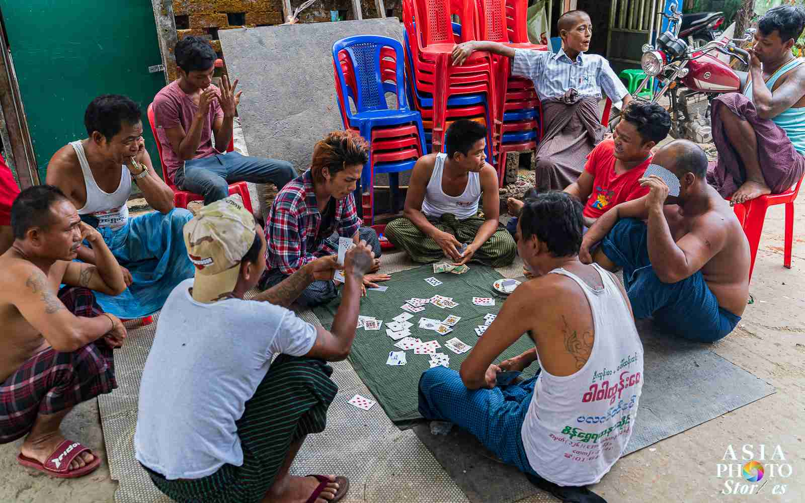 Men play cards in a slum village off the Yangon train line.