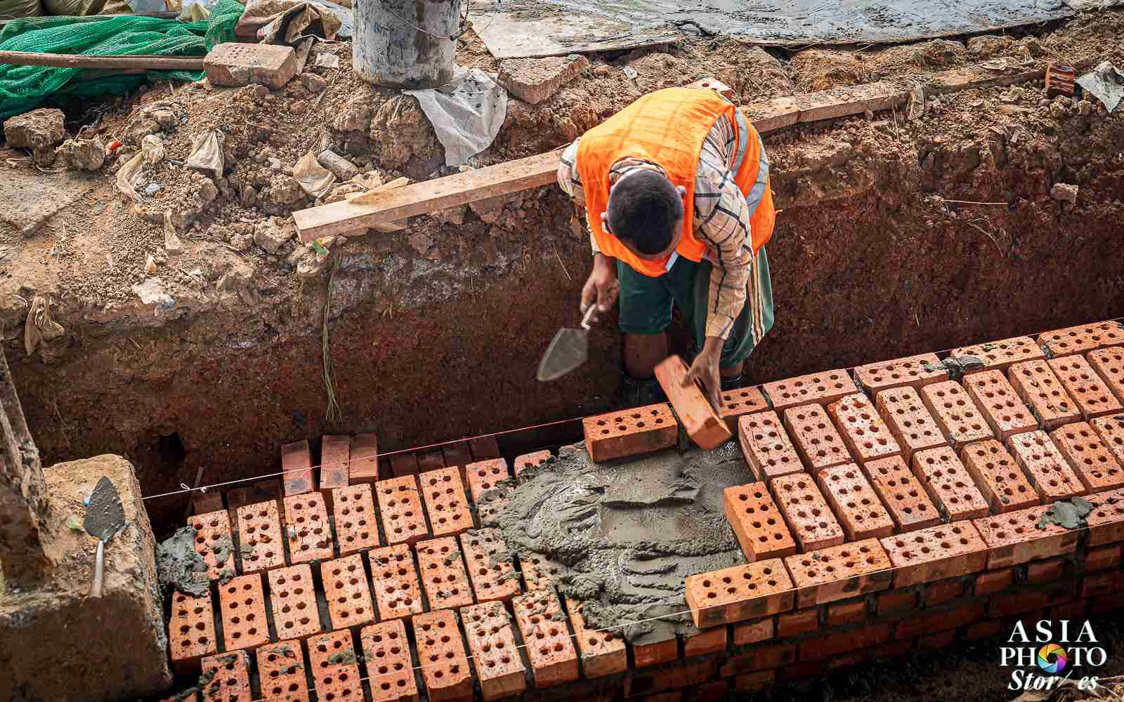 A bricklyaer builds a new platform at a Yangon train station.