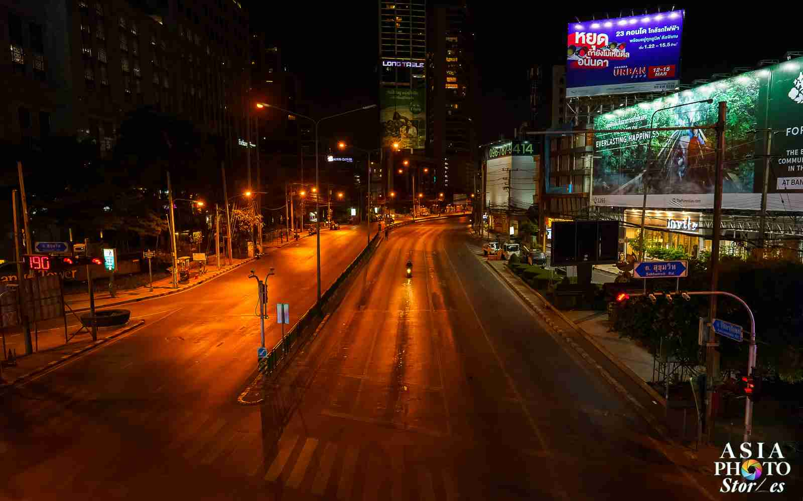 A solitary motorcyclist rides on Asok Montri Road in Bangkok's business district before 9 p.m. on April 2, a night before a national curfew was imposed by the government.