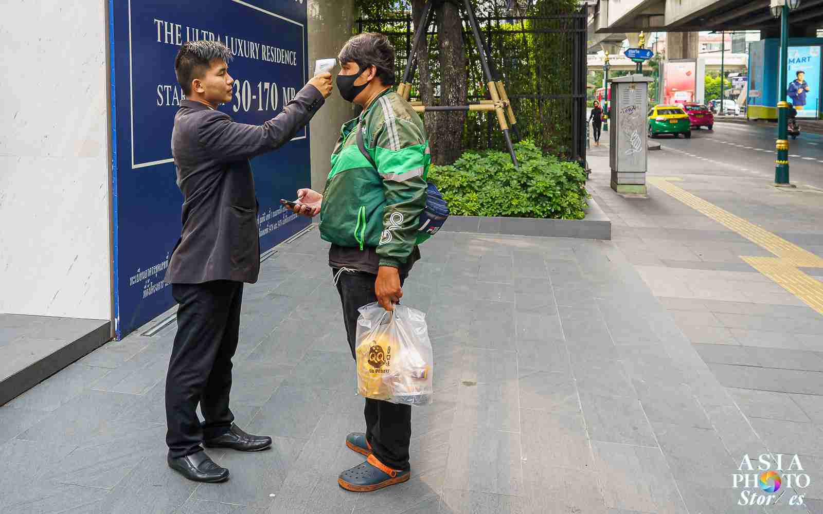 Bangkok, Thailand (April 14, 2020): A condomium security guard checks a food-delivery driver for a fever amid the Covid-19 pandemic.